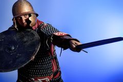 Armor. Portrait of a medieval male knight in armor over blue background stock image