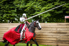 Armored knight on horseback charging in a joust stock photo