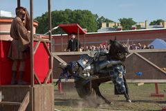Armored knight participating in jousting. St. Petersburg, Russia - July 9, 2017: Armored knight falls off a horse in the jousting tournament during the military Royalty Free Stock Photos