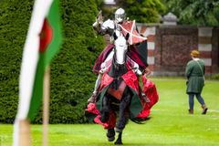Armored knight suited for battle on horseback. Charging in gallop. Galloping it's the fastest gait of a horse, and because of the speed the warrior looks Stock Photo