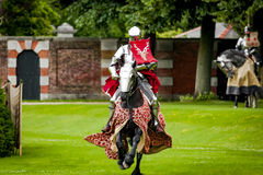 Armored knight suited for battle on horseback. Charging in gallop. Galloping it's the fastest gait of a horse, and because of the speed the warrior looks Royalty Free Stock Photos
