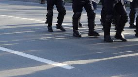 Armored Police Force. Armored police men, wearing on feet and body armor,  marching for law enforcement