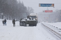 The armored troop-carrier. Of the Ministry of Emergency Situations helps the trucks to overcome snowy rise on the road, Kyiv, Ukraine Stock Photography