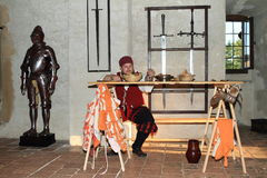 Armory with armor and swords. Soldier dressed in renaissance landsknecht costume in armory with table full of food and armor and swords behind during Night Stock Photography