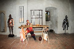 Armory with armors and swords. Soldier dressed in renaissance landsknecht costume in armory with table full of food and armors and swords behind him during Night Stock Images