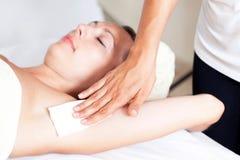 Armpit deplication. Mid-adult woman having an armpit depliation stock photo
