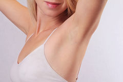 Armpit epilation, lacer hair removal. Young woman holding her arms up and showing underarms, armpit, ideal smooth clear skin Stock Photos