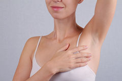Armpit epilation, laser hair removal. Young woman holding her arms up and showing underarms, armpit, ideal smooth clear skin Royalty Free Stock Photos