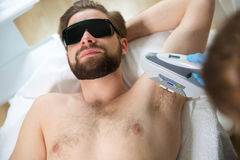 Armpit laser epilation at beautician`s. Men lying at beautician`s during laser armpit hair removal therapy Royalty Free Stock Photography