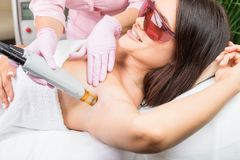 Armpit laser hair removal. Beautiful smiling woman client in red glasses having procedure. Royalty Free Stock Images