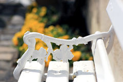 The armrest on the bench. Curved armrest in the form of bunches of grapes on a white bench stock image