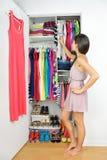 Armário home - mulher que escolhe sua roupa de forma Fotografia de Stock