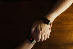 Arms ambraced displaying heart symbols on smart watches Stock Images