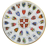 Arms blazon of the Cambrige. Coat of blazon arms of the Cambrige university colleges on porcelain plate mass production public domain images isolated Stock Image