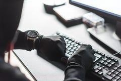 Arms of computer burglar noting down time Stock Image