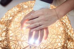 Arms couple with rings lit by bright light. Gold wedding Stock Image