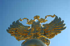 Arms (emblem) of Russia. Gilded Arms (emblem) of Russia. Blue sky on the background Stock Image