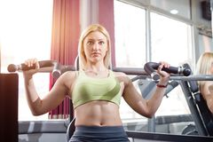 Arms exercise in gym, blonde girl Royalty Free Stock Image