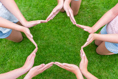 Arms of girls with hands making star shape above grass