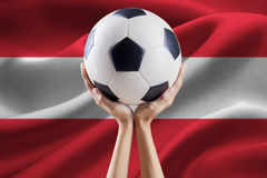 Arms holding ball with flag of Austria Royalty Free Stock Images