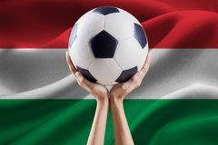 Arms holding ball with flag of Hungary Royalty Free Stock Photos