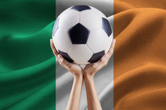 Arms holding ball with flag of Ireland Royalty Free Stock Photo