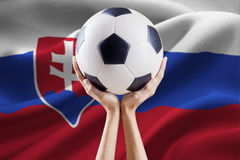 Arms holding ball with flag of Slovakia Stock Image