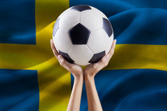 Arms holding ball with flag of Sweden Stock Photography