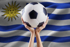 Arms holding ball with flag of Uruguay Stock Photography