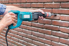 Arms holding drilling machine against brick wall Royalty Free Stock Images