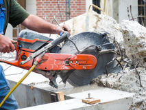 Arms holding grinder cutting concrete. Male arms holding circular grinder cutting concrete Royalty Free Stock Image