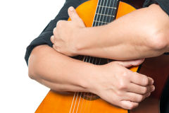 Arms hugging an acoustic guitar Stock Images