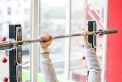 Arms of man working out in the gym, beginner athlete doing bench press exercise royalty free stock image