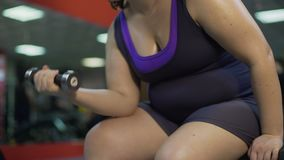 Arms of overweight girl training in gym, doing dumbbell exercise for biceps