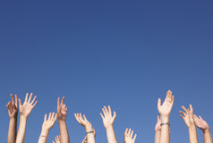 Arms Raised Against Blue Sky. Cropped view of group of people with arms raised against a blue sky. Horizontally framed shot Royalty Free Stock Photography