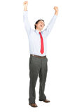 Arms Raised Celebrating Latino Office Worker Yell. A victorious Hispanic male office worker in business clothes screaming, raising his arms and fists in stress Stock Photo