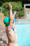 Arms raised little boy standing at poolside Royalty Free Stock Images