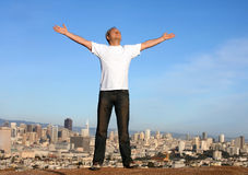 Arms raised over San Francisco. A man standing on a hill with arms raised and the skyline of San Francisco in the background Royalty Free Stock Photo