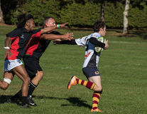 Arms Reach. Redding, California- November 7, 2015: A Highlander player (white jersey) runs down the pitch and evades Blackhawk players in a match between Shasta stock images