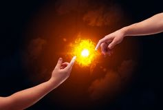 Arms reaching for the sun. Two naked male hands about to touch, lighting a bright flame with smoke in red sky background concept Stock Photography
