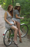The arms trade. Two beautiful girls summer day with bicycle Stock Photography