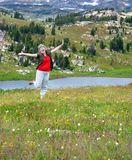 Arms Wide and Celebrating. Older female dancces to celebrate her joy at seeing Beartooth Pass and Little Bear Lake.  Her arms are wide and she is laughing Royalty Free Stock Photo