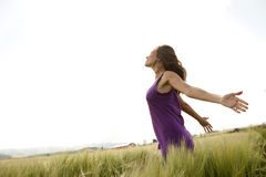 Arms wide open. A woman spreads her arms wide open while out in a field on a sunny day Stock Photo