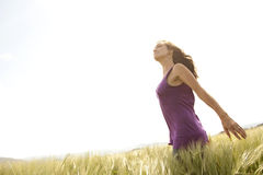 Arms wide open. A woman spreads her arms wide open while out in a field on a sunny day Stock Images
