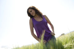 Arms wide open. A woman spreads her arms wide open while out in a field on a sunny day Royalty Free Stock Photos