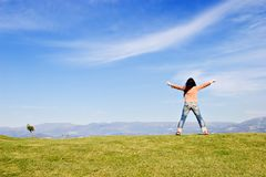 With arms wide open. Woman standing on grass field, with arms wide open Stock Photography