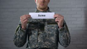 Arms word written on sign in hands of male soldier, weapon arsenal, industry. Stock footage stock video footage