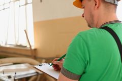 Arms of worker making notes on clipboard with green pen. Closeup. Manual job DIY inspiration improvement fix shop graphic joinery startup workplace idea Royalty Free Stock Photo