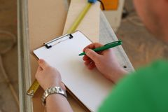 Arms of worker making notes on clipboard with green pen. Closeup. Manual job DIY inspiration improvement fix shop graphic joinery startup workplace idea Royalty Free Stock Images
