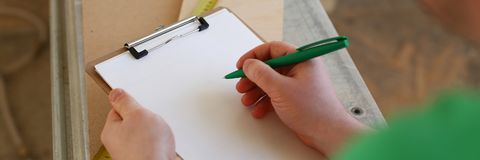 Arms of worker making notes on clipboard with green pen. Closeup. Manual job DIY inspiration improvement fix shop graphic joinery startup workplace idea Stock Photos